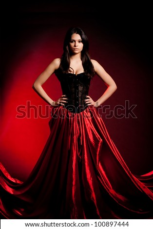 Sexy young woman in fashion dress on red background. - stock photo