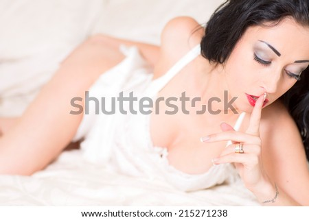 Sexy Young Woman In Lingerie Lying on a Bed - stock photo