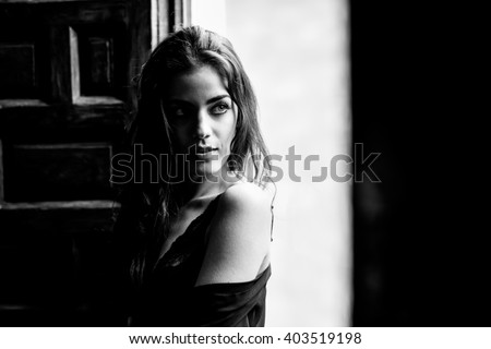 Sexy young woman in lingerie standing near a window in her bedroom. Brunette girl wearing black body and neglige. Female in underwear. Black and white photograph.