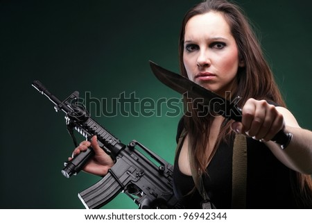 Sexy young woman in red with a gun, knife on green background - stock photo