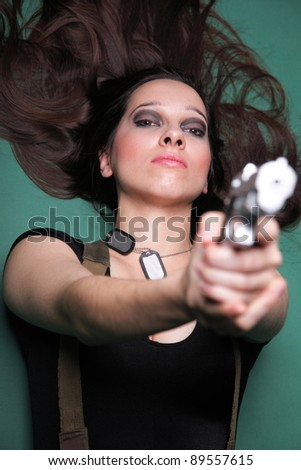 Sexy young woman in red with a gun, on green background