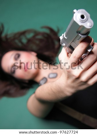 Sexy young woman in red with a gun, on green background - stock photo