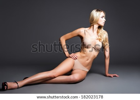 Sexy young woman in underwear sitting on a floor. Studio shot  - stock photo