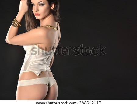 Sexy young woman in white seductive lingerie. photo in dark studio.
