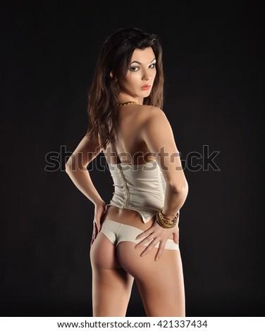 Sexy young woman in white seductive lingerie. photo in dark studio. - stock photo