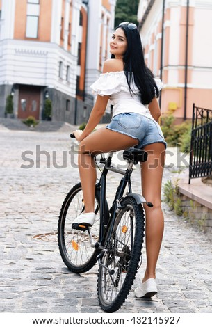 Sexy young woman in white t-shirt and shorts jeans with bike on the street