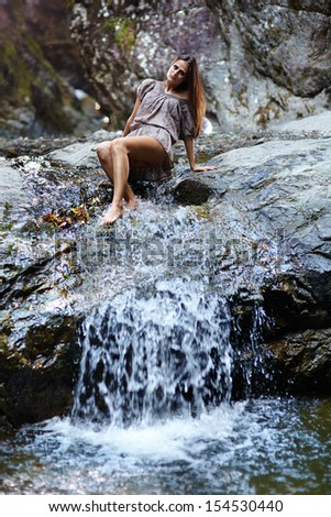 Sexy young woman laying on the mountain rock near a waterfall