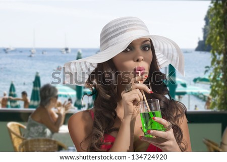 sexy young woman on a bar beach drinking fresh green mint. she has white summer hat - stock photo