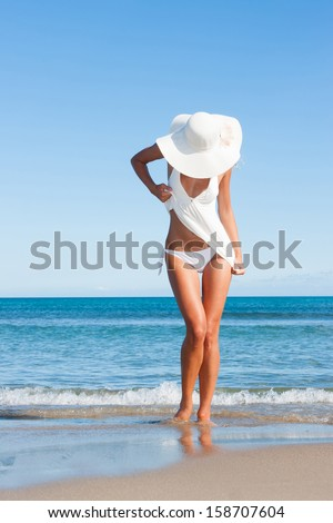 Sexy young woman on the beach in summer dress - stock photo