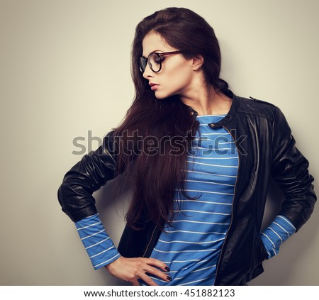 Sexy young woman posing in fashion black leather jacket and glasses. toned vintage closeup portrait