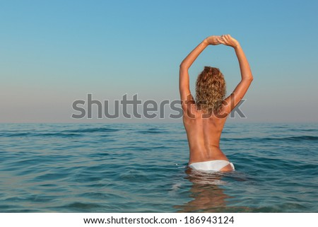 Sexy young woman  posing topless on the beach at sunset - stock photo