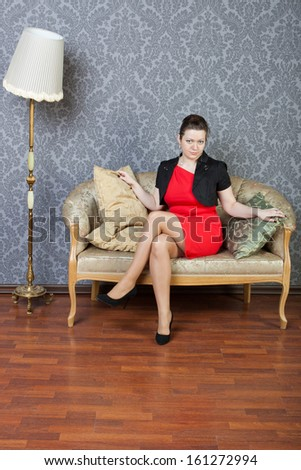 sexy young woman sits on a sofa - stock photo