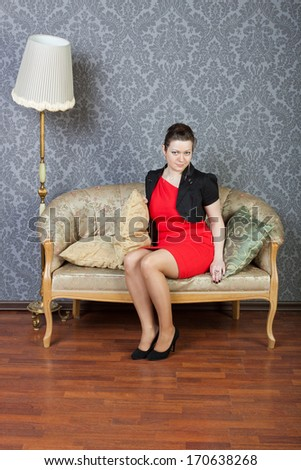 sexy young woman sitting on a sofa - stock photo