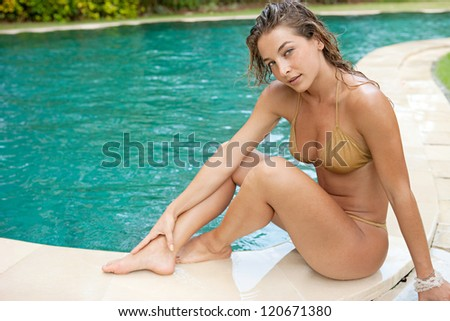 Sexy young woman sitting on the edge of a swimming pool, wearing a gold bikini while on vacations in a sunny destination.