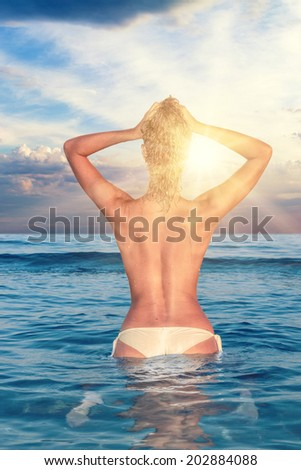 Sexy young woman  topless posing on the beach at sunset - stock photo