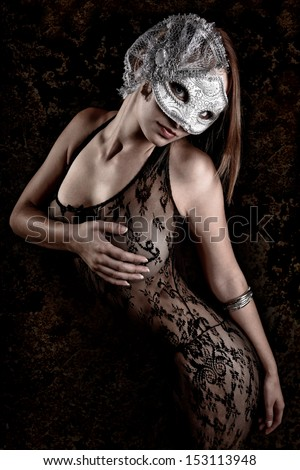 Sexy Young Woman wearing a silver mask and lace body suit. - stock photo