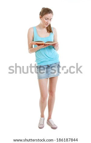 sexy young woman wearing jans mini-skirt, blue t-shirt and gumshoes reads a book - stock photo