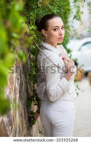 Sexy young woman wearing white pants and jacket posing near the wall - stock photo