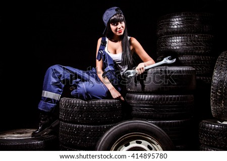 Sexy young woman with a big wrench in a tire service over black background - stock photo
