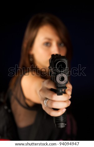 Sexy young woman with a gun isolated on black