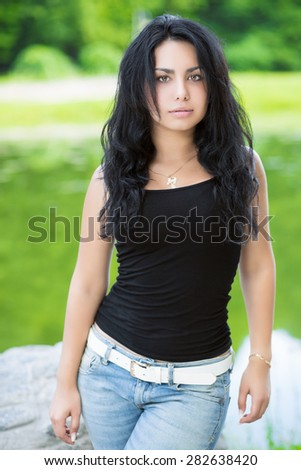 Sexy young woman with curly black hair posing outside - stock photo