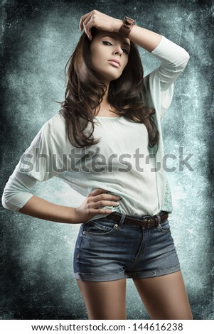 sexy young woman with denim shorts and natural brown hair-style in sensual pose looking in camera on grunge background