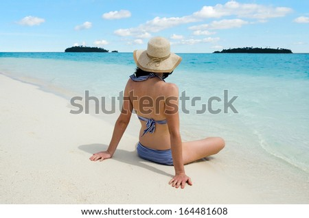 Sexy young woman with hat relaxing on Aitutaki Lagoon, Cook Islands. women freedom, travel, vacation ,happy, happiness, solo, alone, single, fun.