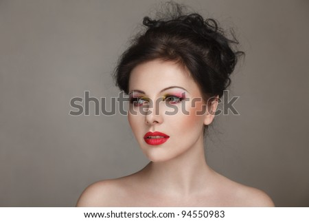 Sexy young woman with naked shoulders looking sidewards studio portrait