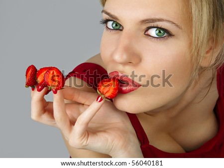 Sexy young woman with red strawberries picked on fingertips isolated on gray background - stock photo