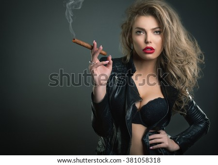 Sexy young woman with sigar on dark background studio shot - stock photo