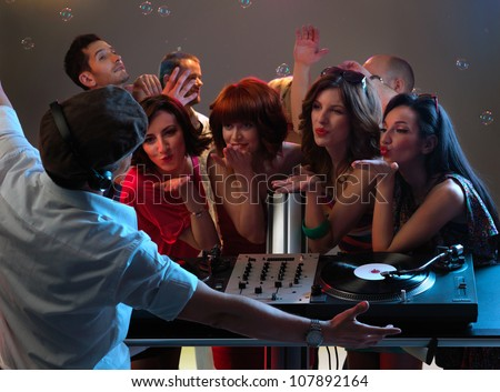 sexy, young women dancing and blowing kisses to the dj in a night club - stock photo