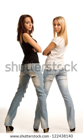 Sexy young women in tight fitting jeans standing side by side with their backs to the camera looking back over their shoulders isolated on white