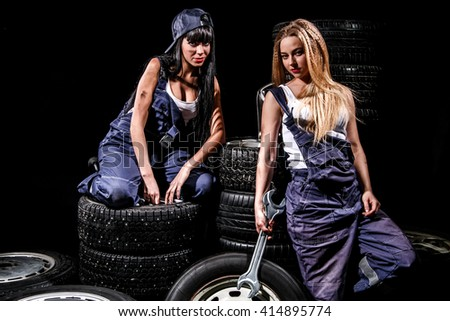 Sexy young women with a big wrench in a tire service over black background - stock photo