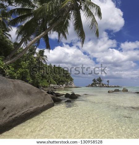 Seychelles. Granite rocks and turquoise sea. White sand and warm water of tropics. Beautiful vacation spot and admiring nature. - stock photo