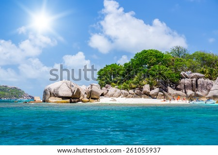 Seychelles, motor boat against the tropical backdrop of the rocky island. People bathe. Sunny day.