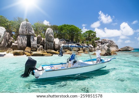 Seychelles, motor boat against the tropical backdrop of the rocky island. Sunny day.