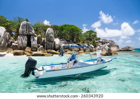 Seychelles, motor boat against the tropical backdrop of the rocky island. Sunny day. - stock photo