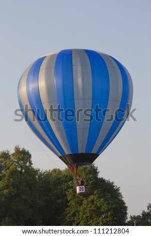 SEYMOUR, WI - AUGUST 3: A Silver and blue striped hot air balloon lifting off at the Balloon Rally at the Annual Hamburger Festival on August 3, 2012 in Seymour, Wisconsin.