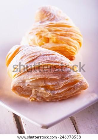 Sfogliatelle, typical Italian pastries, over white plate - stock photo