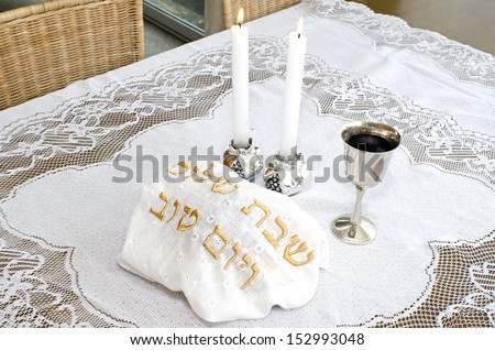 Shabbat eve table with covered challah bread, candles and cup of wine. - stock photo