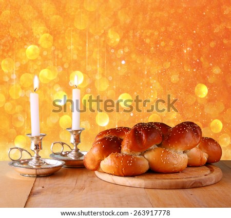 shabbat image. challah bread and candelas on wooden table. glitter overlay image.  - stock photo