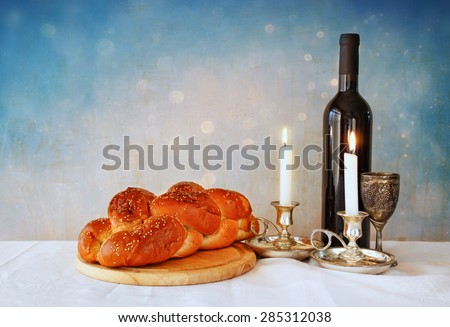 shabbat image. challah bread, shabbat wine and candelas on wooden table. glitter overlay  - stock photo