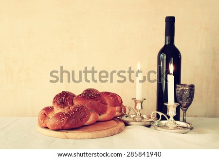 shabbat image. challah bread, shabbat wine and candelas on wooden table. vintage filtered image  - stock photo