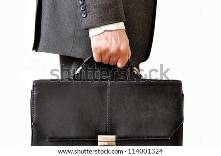 Shabby black leather briefcase in male hand - stock photo