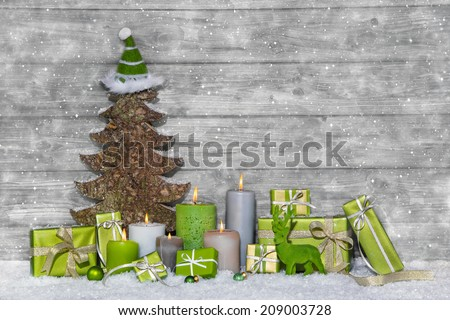 Shabby chic green and white christmas decoration on grey wooden background with snowflakes. - stock photo