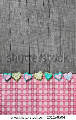 Shabby chic grey wooden background with hearts on a pink white checkered frame. - stock photo