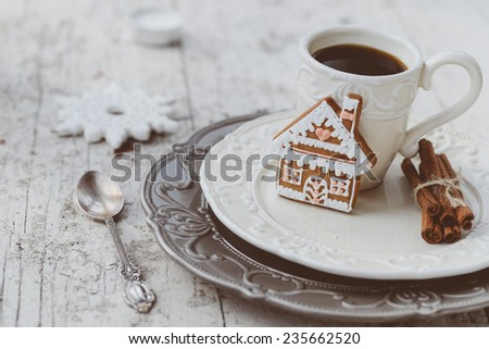 Shabby chic style coffee cup and plate with gingerbread house cookie, cinnamon sticks and other decorations for Christmas mood - stock photo