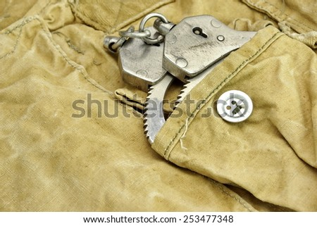 Shabby Handcuffs in the Pocket Close Up - stock photo