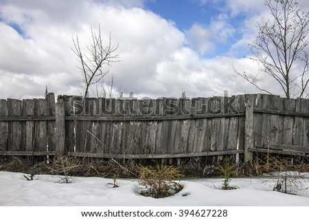shabby rustic wooden fence from boards in village at winter and clear blue sky with clouds