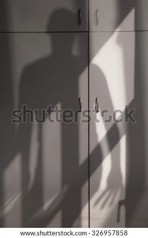 Shade of monster on a domestic cabinet - stock photo